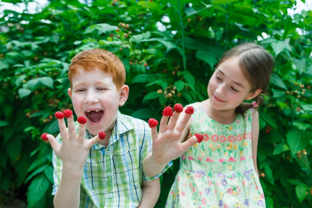 Kids with berries on their fingertips