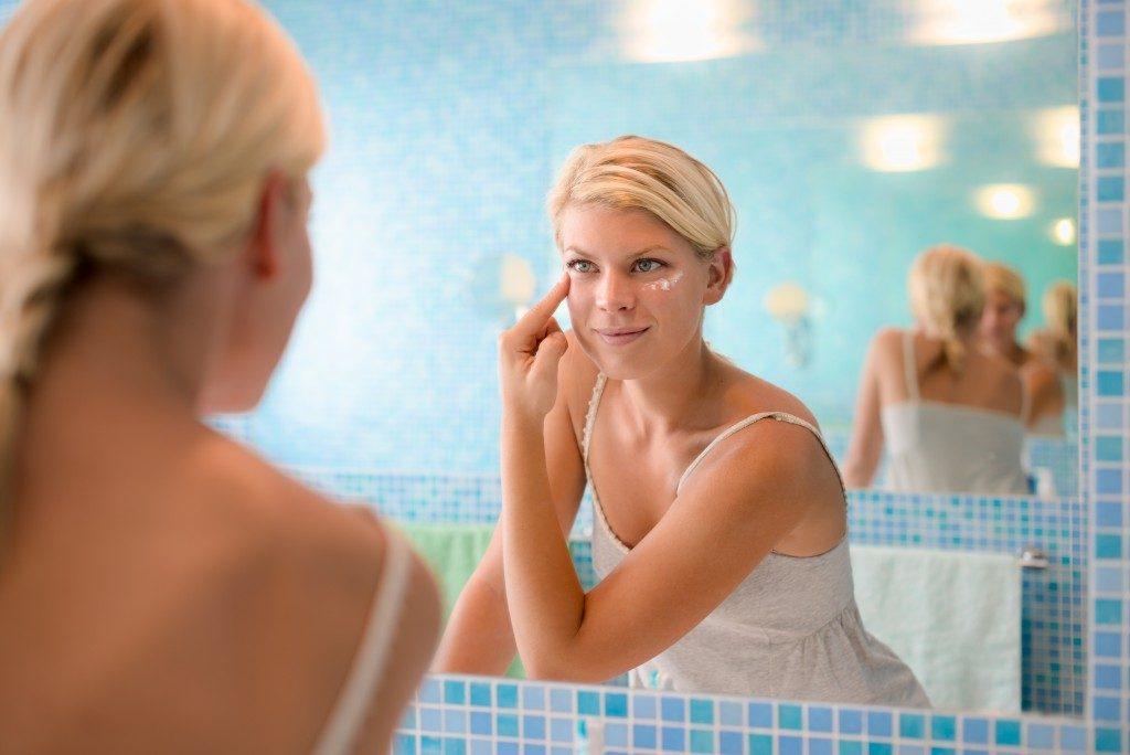 Woman putting an eye cream