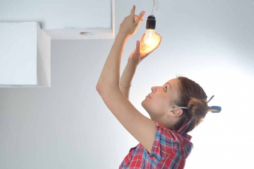 girl replacing light bulb