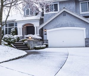 suburban home with snow on drive way