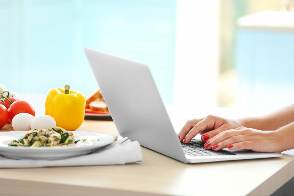 woman eating while using laptop