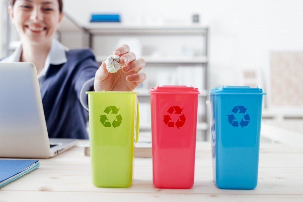 woman throws trash in colored bins