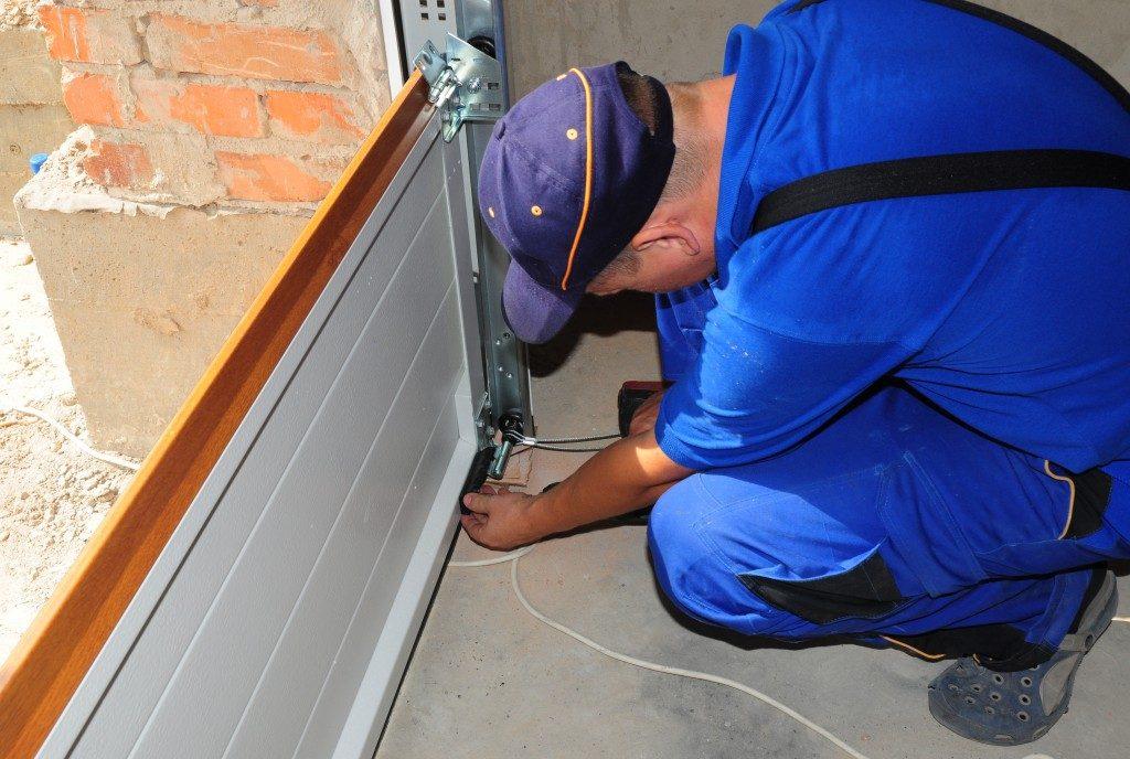 man sealing garage door creases