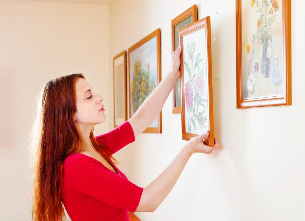 Woman hanging artworks