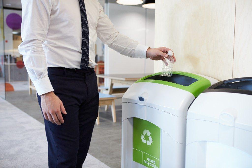 man throwing plastic bottle in the bin
