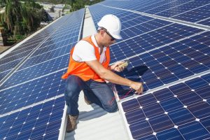 technician checking solar panels on factory roof
