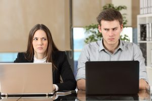 two angry businesspeople using computers