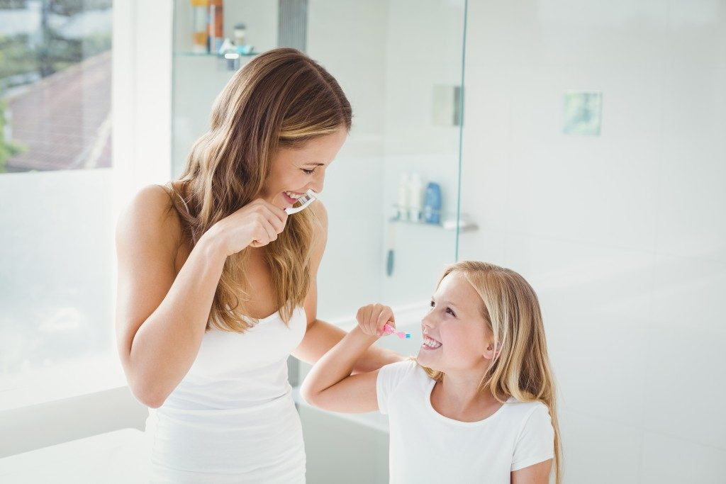 Parent teaching daughter to brush teeth