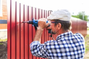 man placing a fence around his home