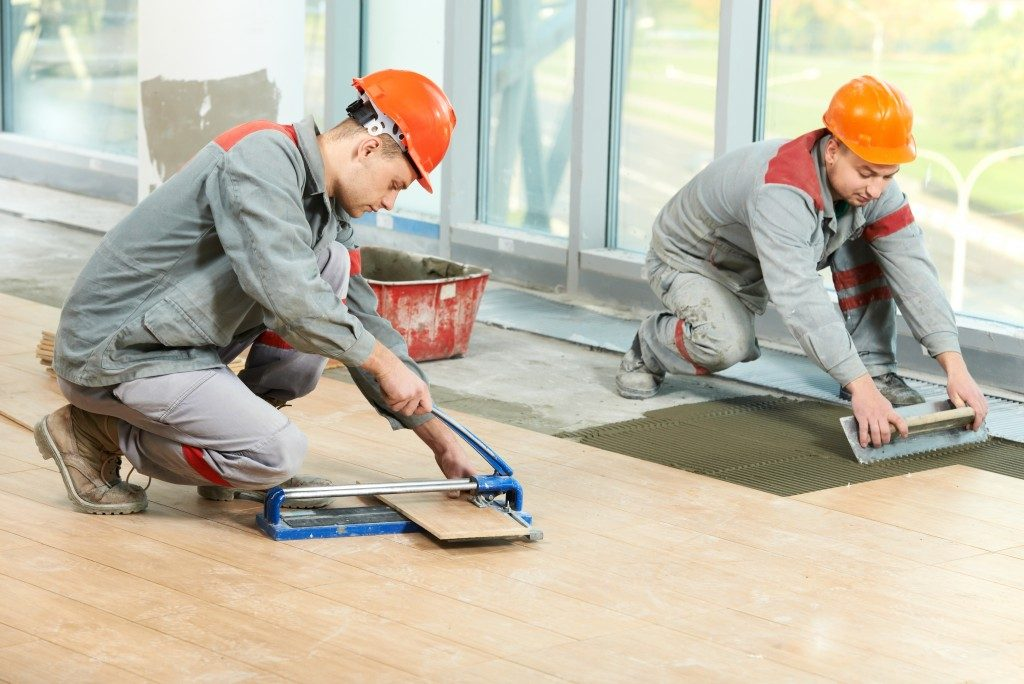 construction workers installing wood tiles