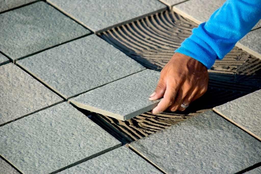close up of a hand installing a floor tile