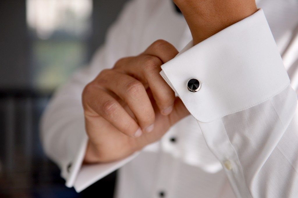 Close up of man hand fixing cufflink