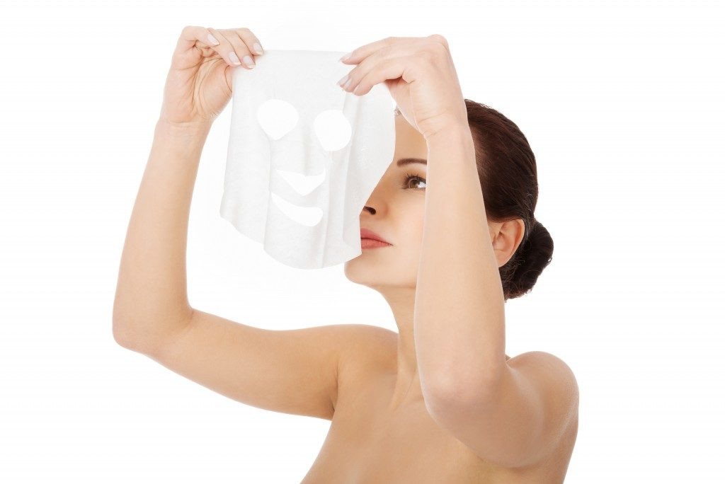 Woman putting on a facial collagen mask