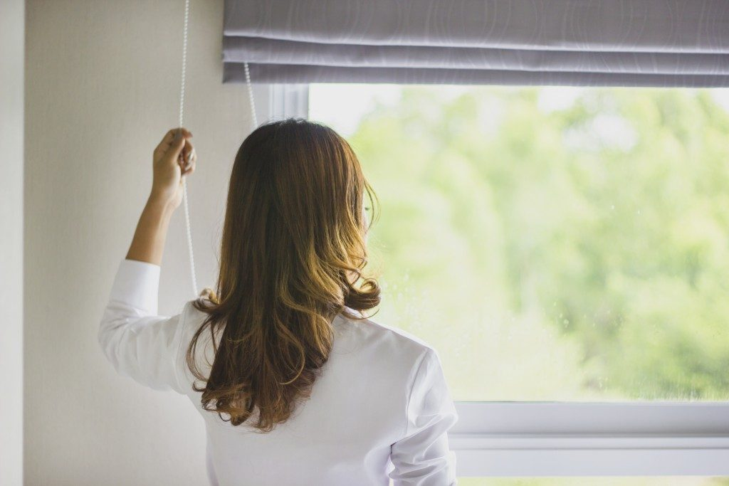 Woman closing window blinds