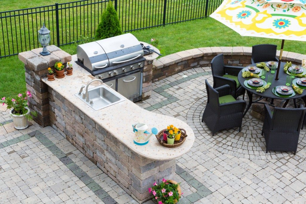 High angle view of a stylish outdoor kitchen, gas barbecue and dining table