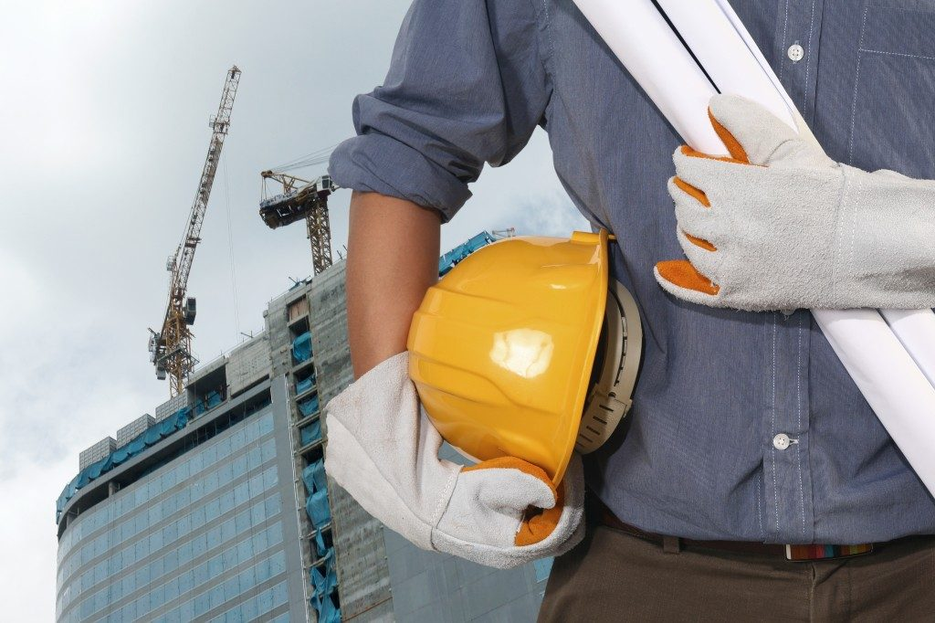 Building contractor holding plans and helmet