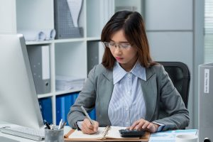 young professional bookeeper writing financial document