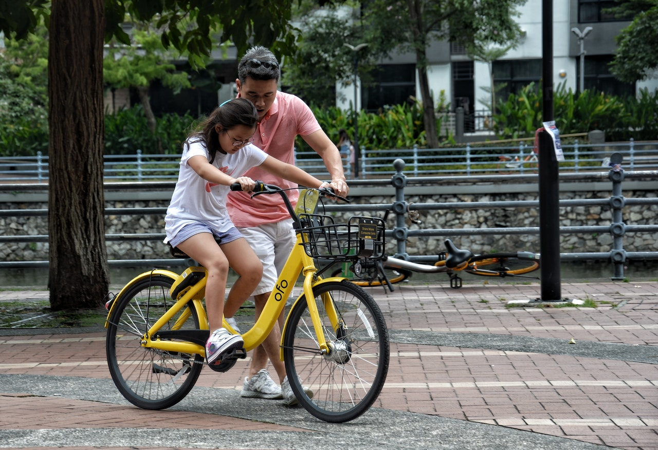 girl learning how to ride a bike