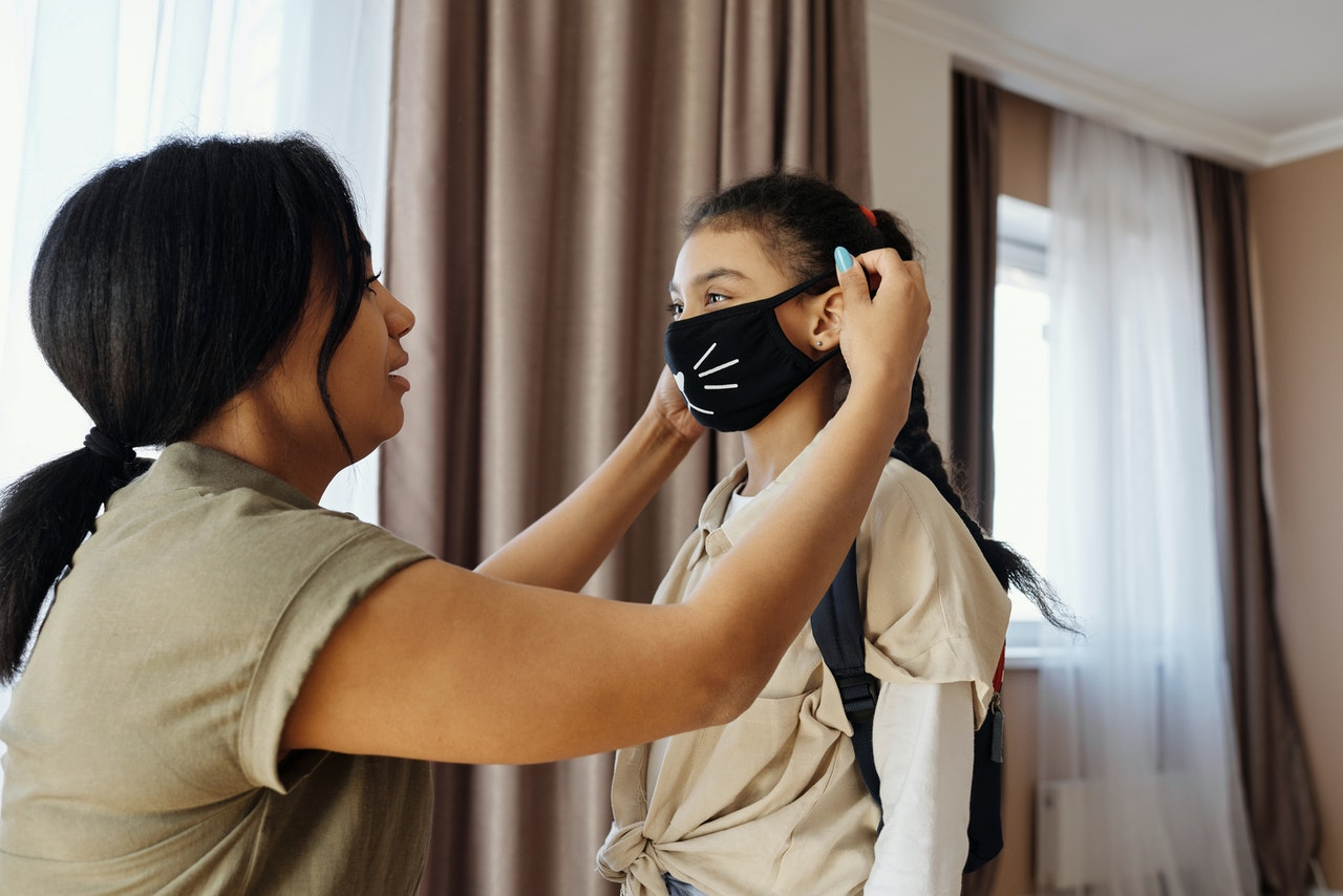 mom putting her daughter's mask on