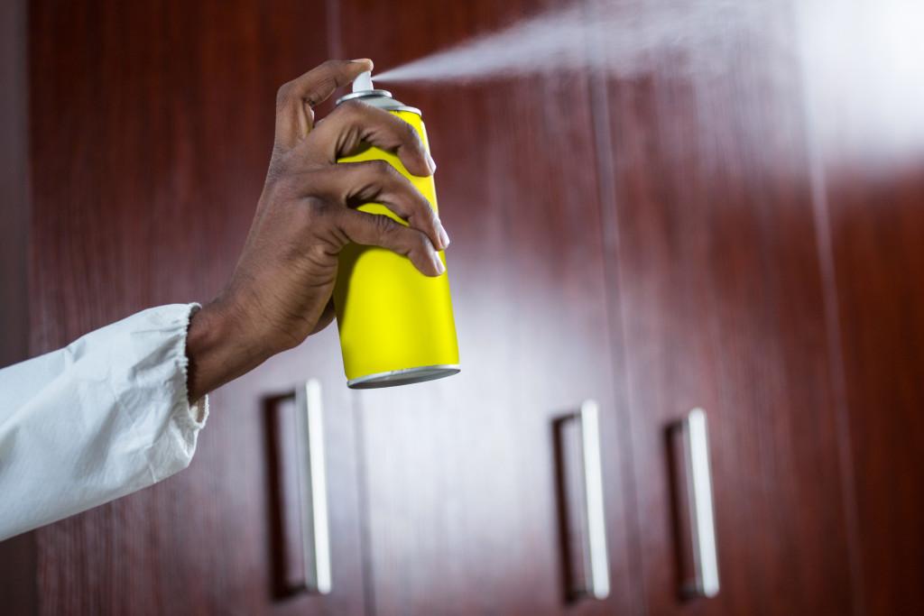 spraying mosquito repellent
