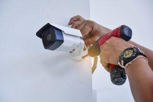 man installing security camera