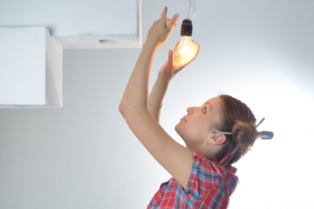 woman changing the lightbulb