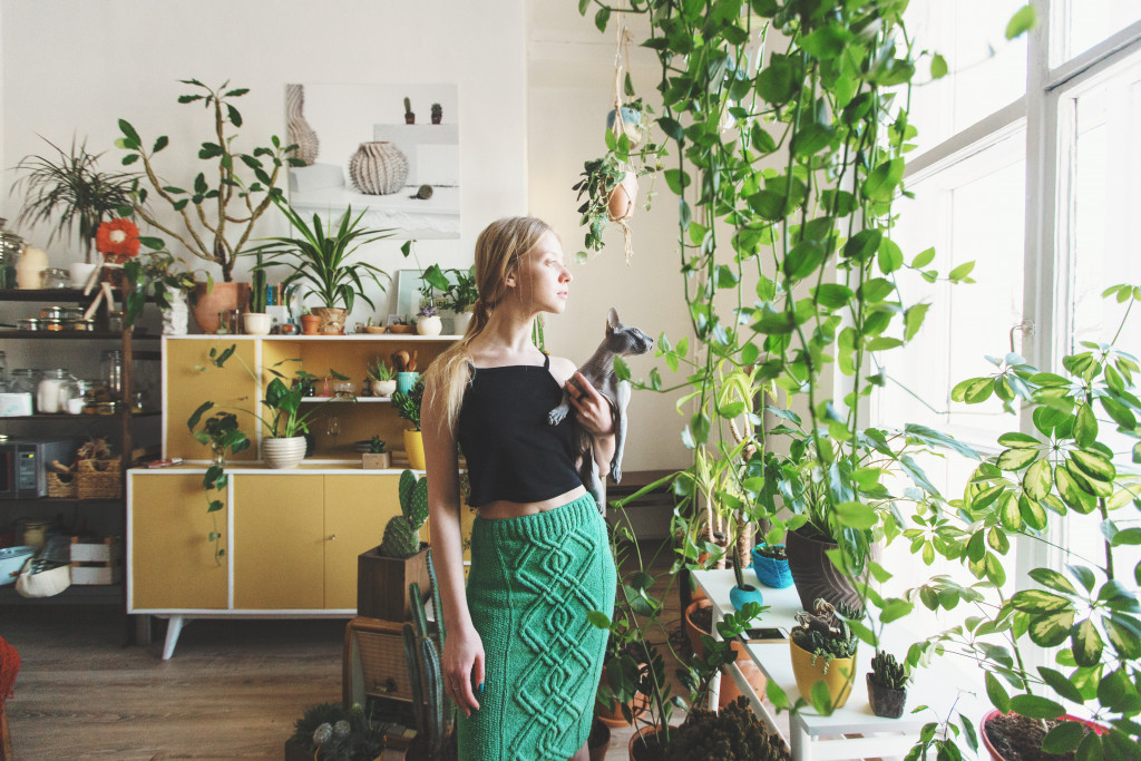 woman holding cat with plants indoors